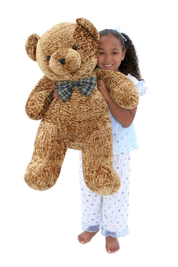Una bella ragazza di sei anni in pigiami con l'orso gigante dell'orsacchiotto fotografia stock libera da diritti