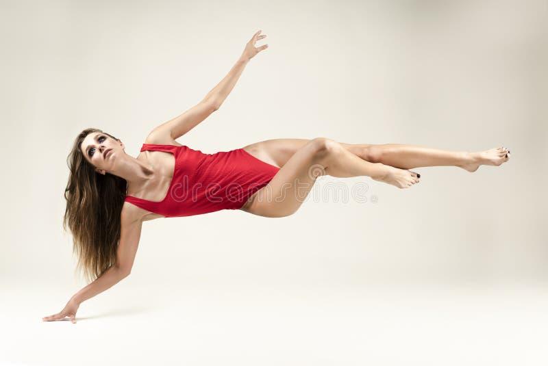 Una bella ragazza esile con le gambe lunghe dai capelli lunghi che indossa un corpo rosso levita su un fondo bianco, toccante il  fotografia stock libera da diritti