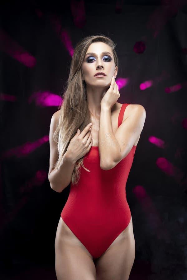Una bella ragazza esile dai capelli lunghi che indossa una tuta rossa sensuale tocca il suo fronte con le sue mani, stanti contro fotografia stock