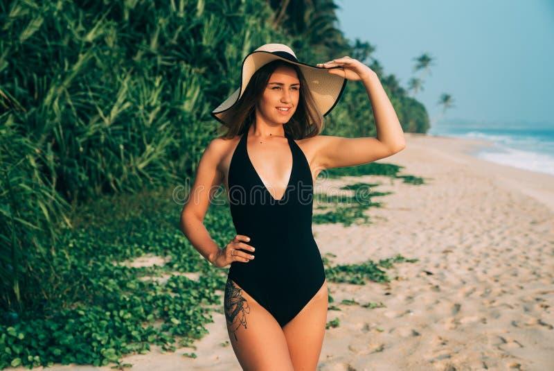 Una bella ragazza europea con un tatuaggio sulla sua anca passeggia lungo la spiaggia in un costume da bagno nero, la copre occhi immagine stock libera da diritti
