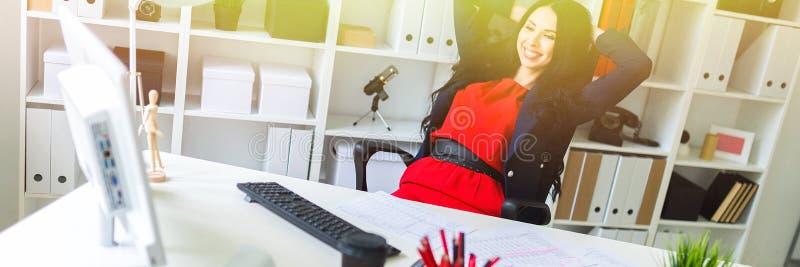 Una bella ragazza ha peso indietro nel suo ufficio alla tavola fotografia stock