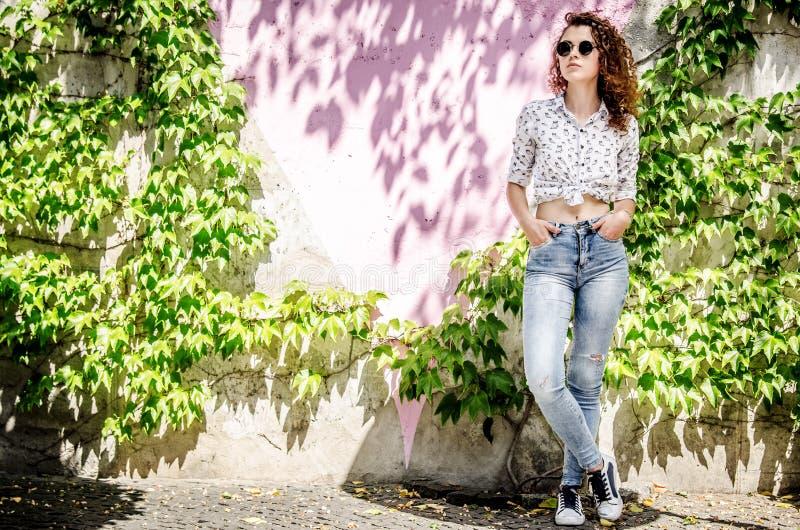 Una bella ragazza in jeans, in scarpe da tennis ed in una camicia sta contro lo sfondo di una parete multicolore, intrecciata con immagine stock