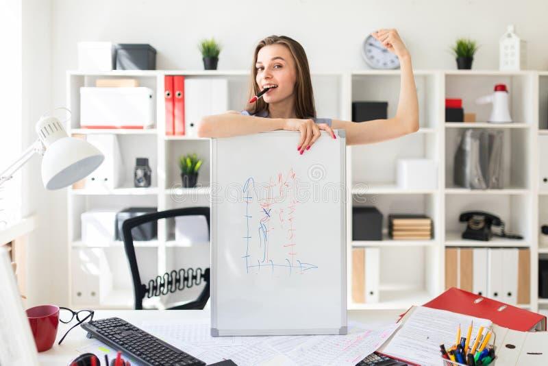 Una bella ragazza nell'ufficio sta stando vicino alla tavola, messa la sua mano sul bordo magnetico, tenute un indicatore rosa fotografia stock libera da diritti
