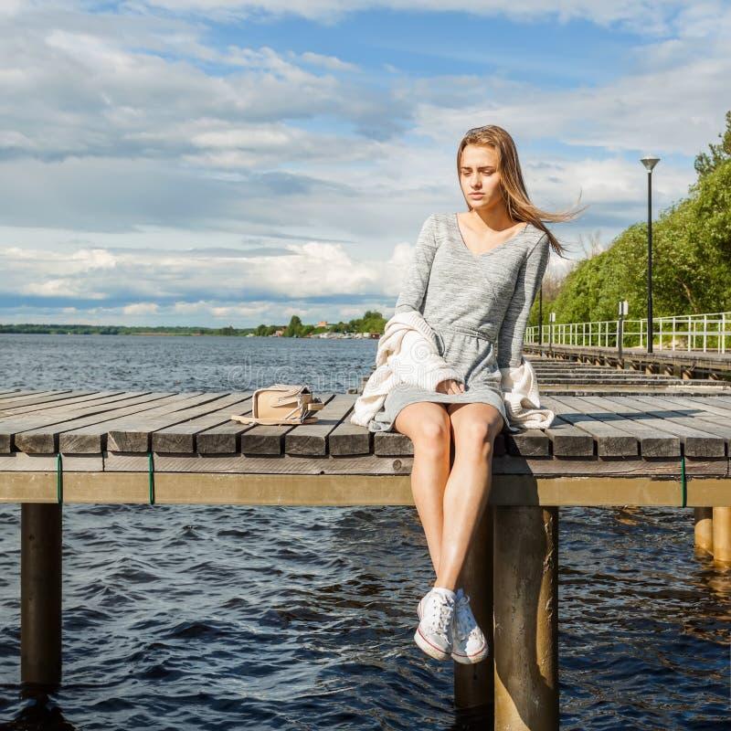 Una bella ragazza si siede da solo su un pilastro del fiume sotto un chiaro sole e sugli sguardi all'acqua Il vento sviluppa i su fotografia stock