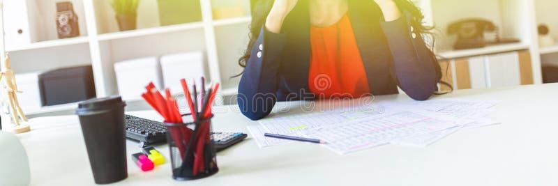 Una bella ragazza si siede nell'ufficio alla tavola e tiene le sue mani dietro la sua testa immagini stock