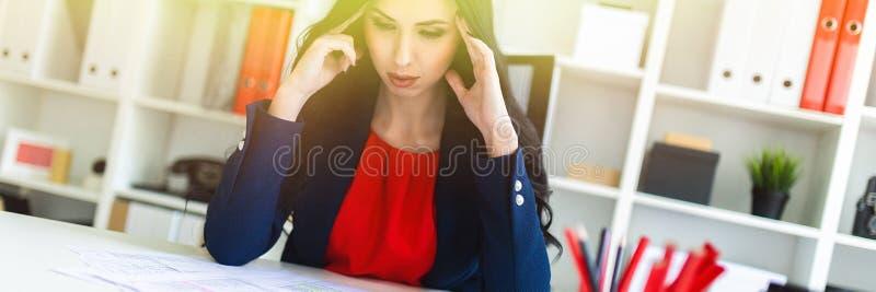 Una bella ragazza si siede nell'ufficio alla tavola e tiene le sue mani dietro la sua testa fotografie stock libere da diritti
