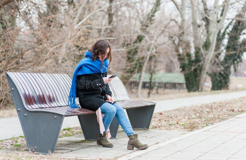 Una bella ragazza sola che si siede da solo e depressa sul banco nella sensibilità del parco abbandonata e denunciata dal suo rag immagini stock libere da diritti