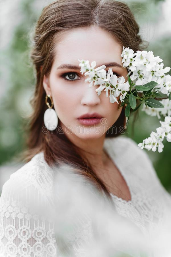Una bella ragazza sta fra gli alberi di fioritura fotografia stock libera da diritti