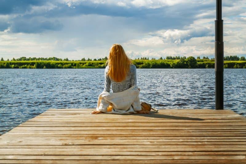 Una bella ragazza sta sedendosi da solo sul pilastro del fiume contro il contesto delle nuvole temporalesche e esamina la distanz fotografia stock
