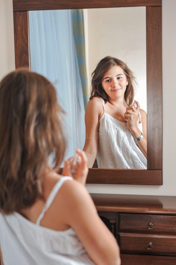 Una bella ragazza teenager studia il suo aspetto mentre esamina lo specchio fotografia stock