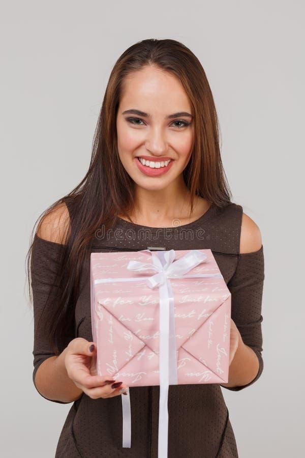 Una bella ragazza tiene un contenitore di regalo rosa e sorride con felicità isolamento fotografia stock libera da diritti