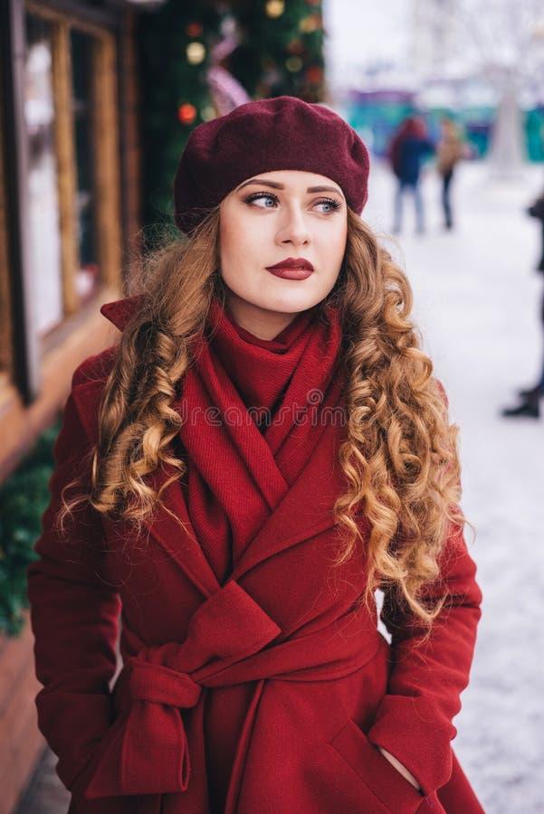 Una bella ragazza in un cappotto rosso ed in un berretto sta camminando lungo la via di Natale fotografie stock