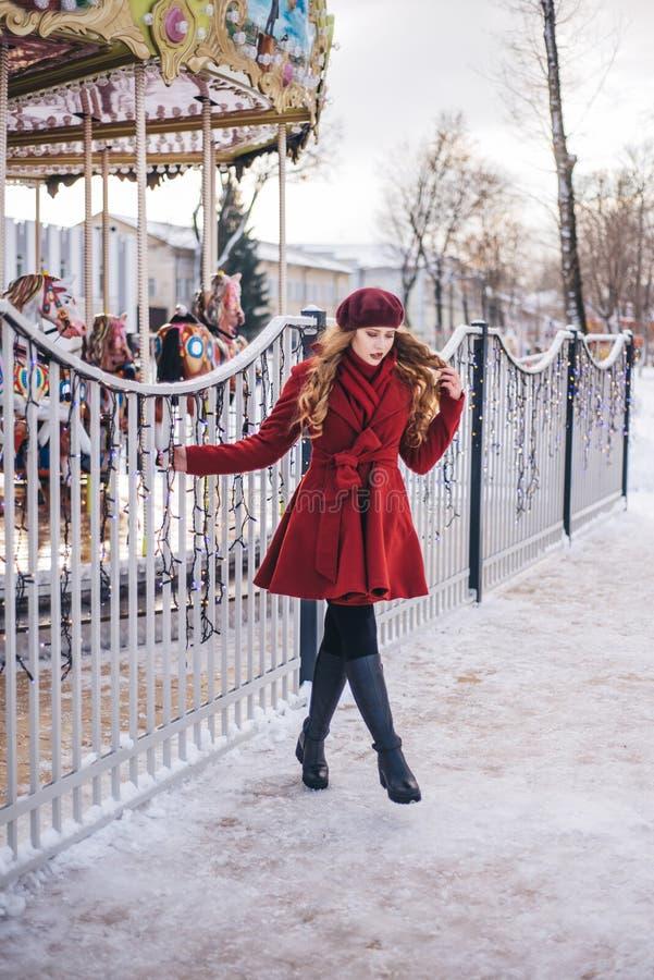 Una bella ragazza in un cappotto rosso ed in un berretto sta camminando lungo la via di Natale immagine stock