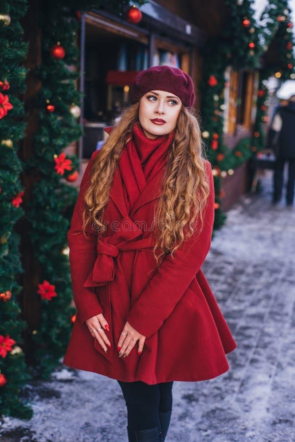 Una bella ragazza in un cappotto rosso ed in un berretto sta camminando lungo la via di Natale immagini stock libere da diritti