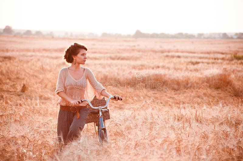 Una bella ragazza in un giacimento dorato della segale romanticamente viene con una bicicletta su cui regali immagini stock