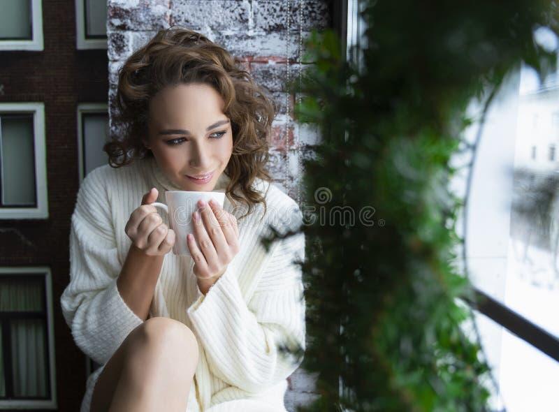 Una bella ragazza in un maglione bianco e nei calzini caldi sta sedendosi sopra fotografia stock