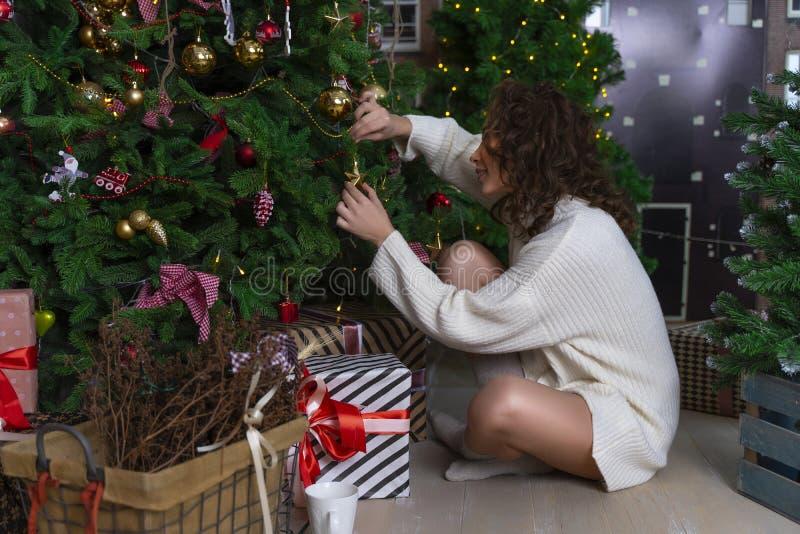 Una bella ragazza in un maglione bianco sta sedendosi fra il Natale t fotografie stock libere da diritti