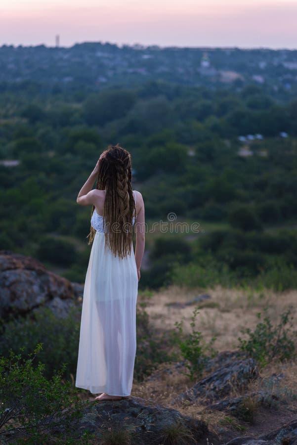 Una bella ragazza in un vestito bianco con i dreadlocks sta stando su una roccia Vista posteriore Contro il cielo di tramonto fotografie stock libere da diritti