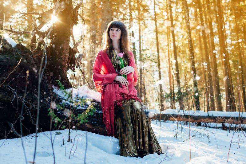 Una bella ragazza in un vestito dall'oro si siede in una foresta soleggiata della molla con un tulipano in sue mani immagine stock libera da diritti