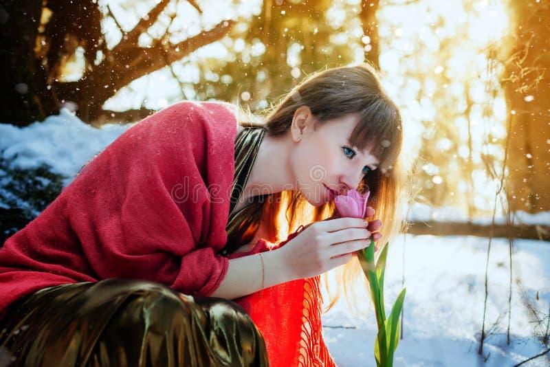 Una bella ragazza in un vestito dall'oro si siede in una foresta soleggiata della molla e tocca un tulipano fotografie stock