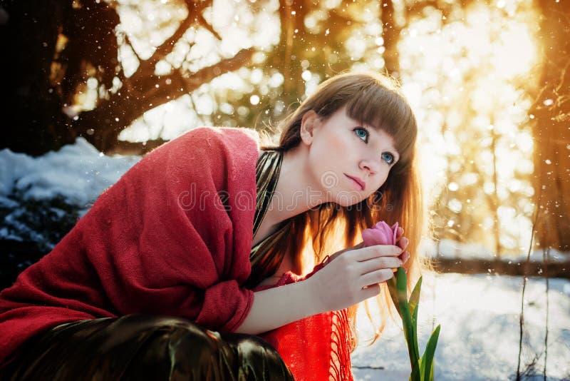 Una bella ragazza in un vestito dall'oro si siede in una foresta soleggiata della molla e tocca un tulipano fotografia stock libera da diritti