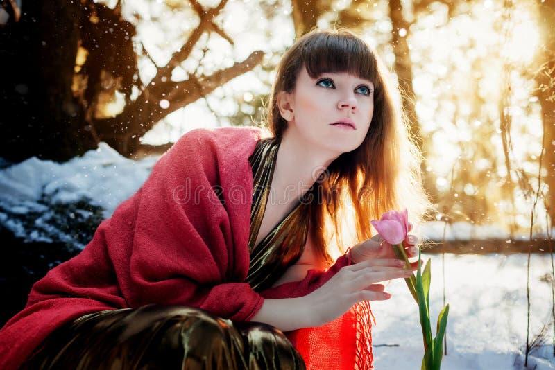 Una bella ragazza in un vestito dall'oro si siede in una foresta soleggiata della molla e tocca un tulipano fotografia stock