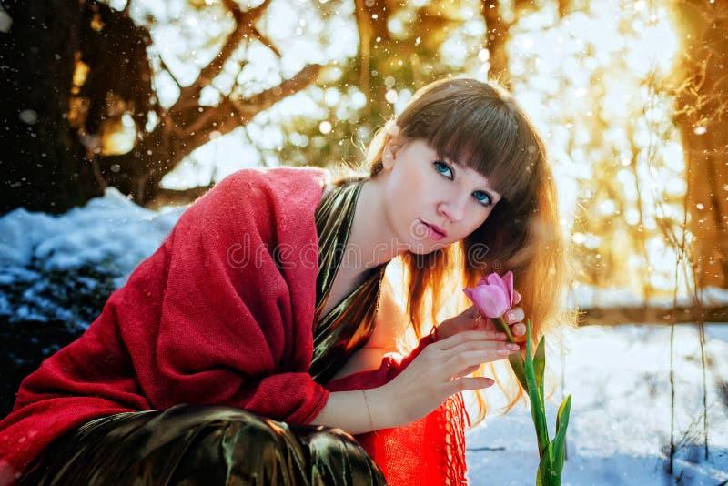 Una bella ragazza in un vestito dall'oro si siede in una foresta soleggiata della molla e tocca un tulipano immagini stock