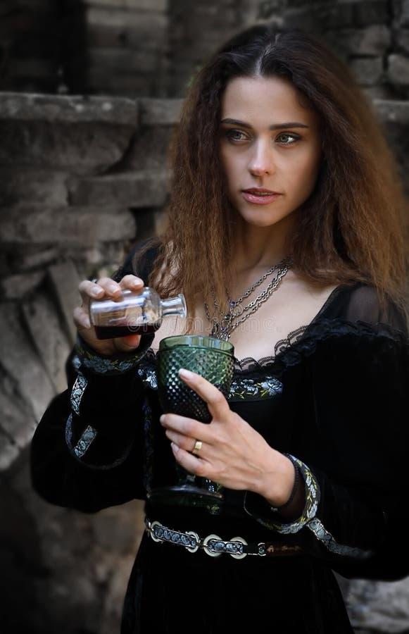 Una bella ragazza versa un certo veleno in un vetro fotografia stock libera da diritti