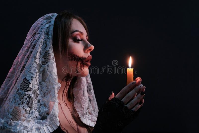 Una bella ragazza vestita come suora terribile tiene una candela accesa Ritratto della donna con trucco di Halloween Concetto per fotografia stock libera da diritti
