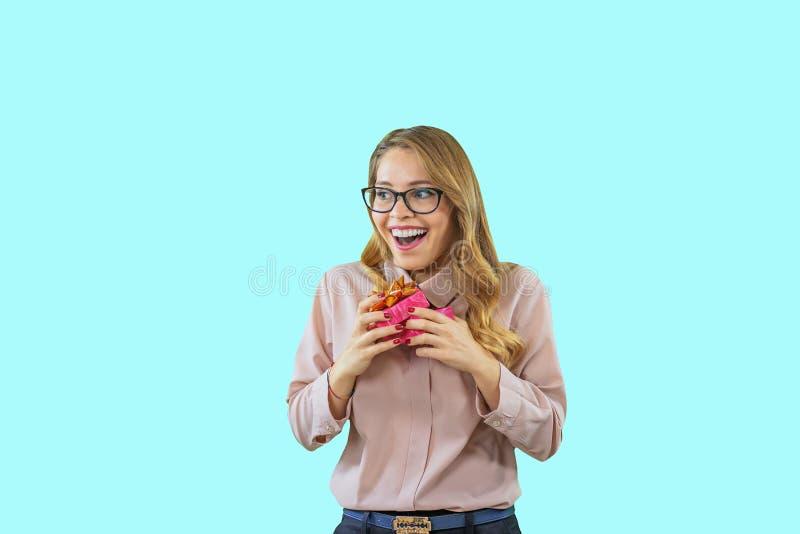 Una bella ragazza in vetri ed in una blusa rosa sta giudicando un regalo sguardo francamente contentissimo e d'esultanza al immagine stock