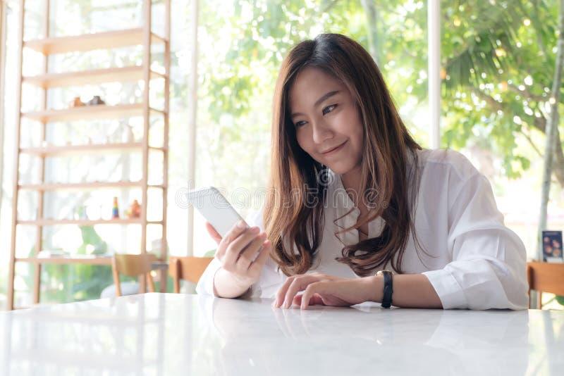 Una bella tenuta asiatica della donna, per mezzo ed esaminando dello Smart Phone con ritenere felice fotografia stock
