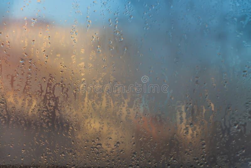 Una bella vista della città di autunno attraverso il vetro appannato bagnato immagine stock