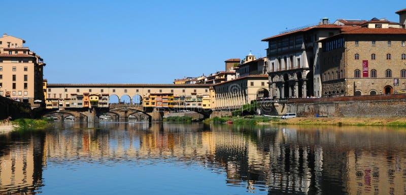 Una bella vista di vecchio ponte famoso Ponte Vecchio e della galleria di Uffizi con cielo blu a Firenze come visto dal fiume di  fotografia stock libera da diritti