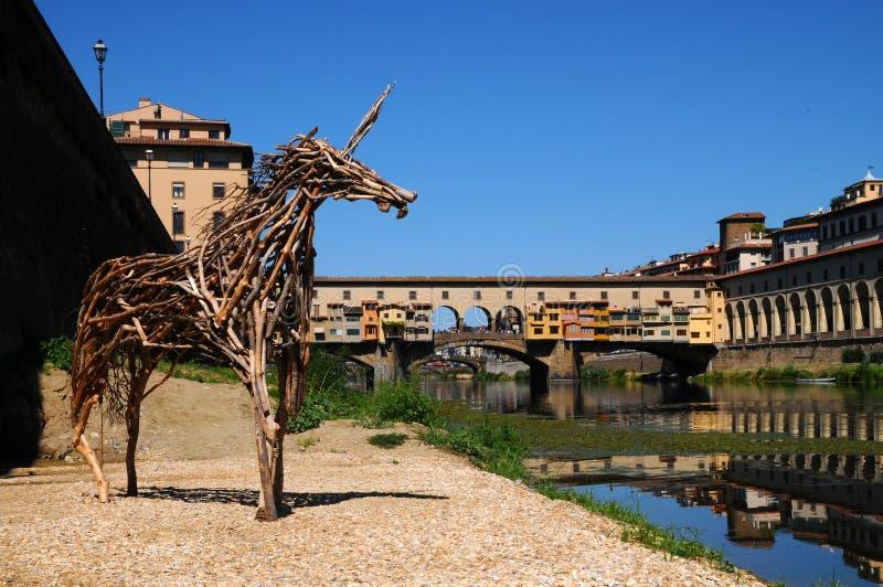 Una bella vista di vecchio ponte famoso Ponte Vecchio e della galleria di Uffizi con cielo blu a Firenze come visto da Arno fotografia stock libera da diritti