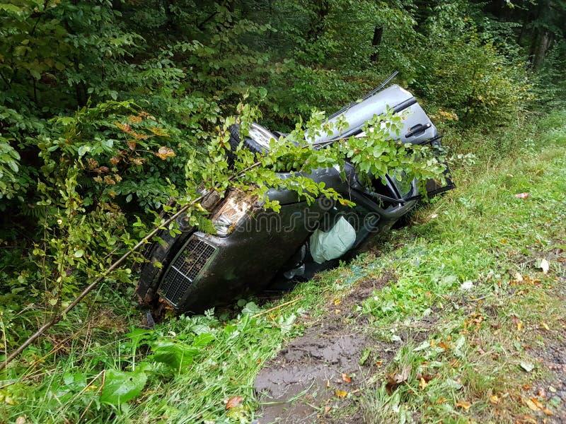 Una berlina grigia avariata dell'automobile si trova in una fossa del bordo della strada fra il fogliame verde fertile del cespug fotografie stock
