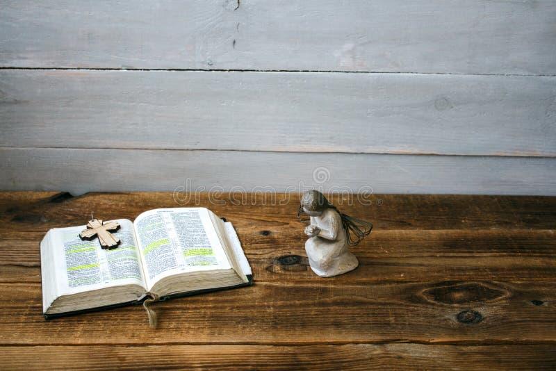 Una bibbia e un incrocio aperti di angelo immagine stock libera da diritti
