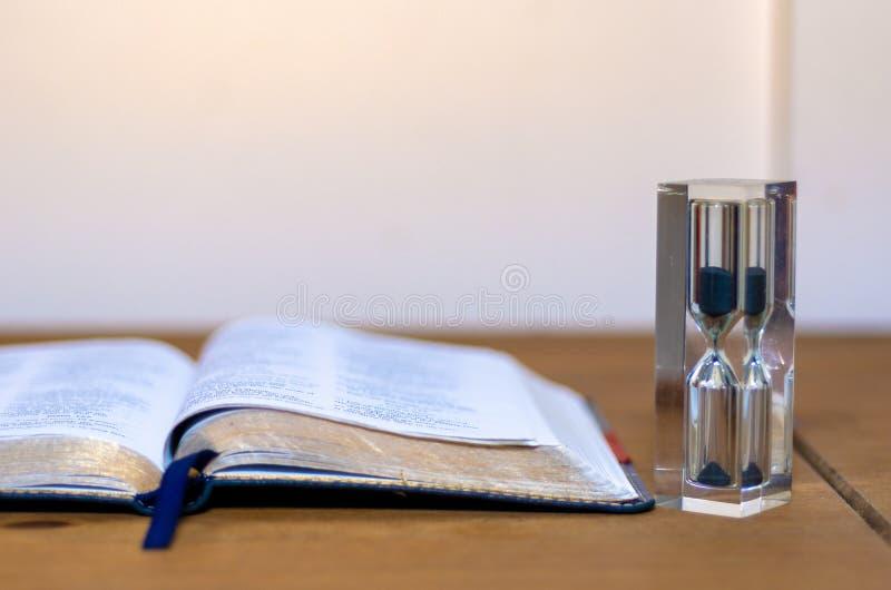 Una biblia abierta por un reloj de arena imagen de archivo