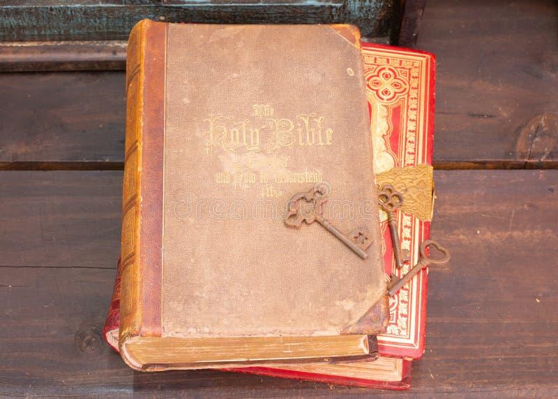 Una biblia antigua y otro libro en un estante de madera con algunas viejas llaves maestras fotos de archivo libres de regalías