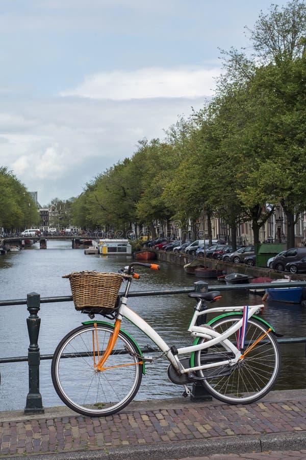 Una bici colourful è sul ponte vicino al canale a Amsterdam fotografie stock