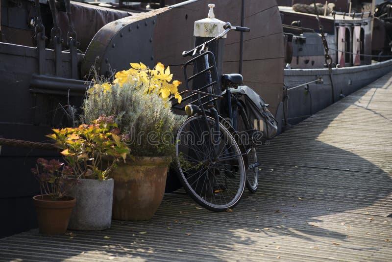 Una bici vieja negra del vintage encadenada a un polo del muelle con los bolsos en el lado fotografía de archivo libre de regalías