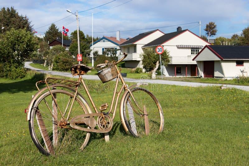 Una bici y casas locales de madera en el pueblo de Dyrnes en la isla de Smola, Noruega foto de archivo libre de regalías
