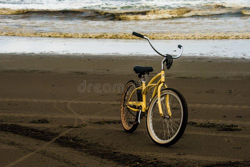 Una bicicleta sola en una playa durante Autumn Evening With The Ocean tempestuoso de Long Beach Washington In The Background foto de archivo