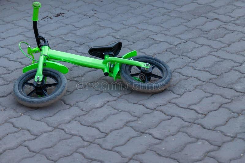 Una bicicletta a due ruote dei piccoli bambini delle bugie di colore verde dal suo lato sulle mattonelle della via di colore grig fotografie stock