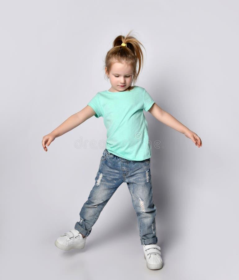 Una bimba bionda con capelli di coda in abiti casuali ed eleganti e scarpe da ginnastica sta bilanciando un piede fotografia stock