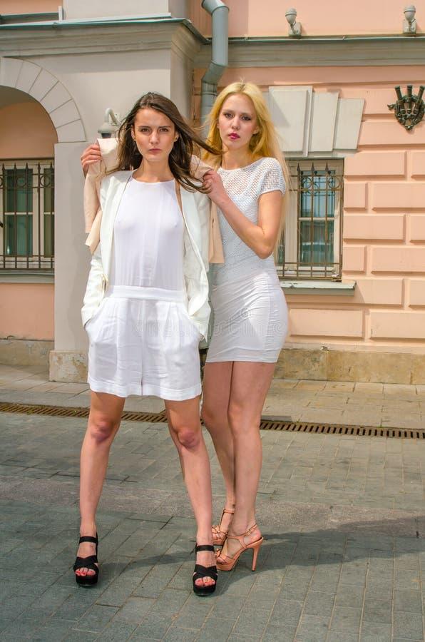 Una bionda di due amici e castana in vestiti bianchi che posano sulla via di vecchia città fotografia stock libera da diritti
