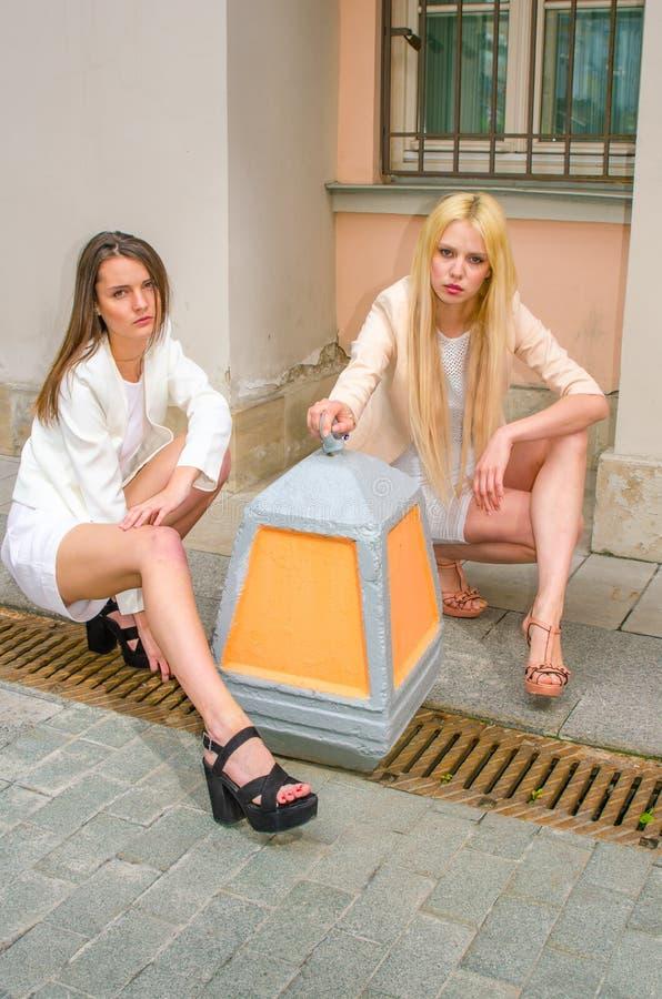 Una bionda di due amici e castana in vestiti bianchi che posano sulla via di vecchia città immagine stock