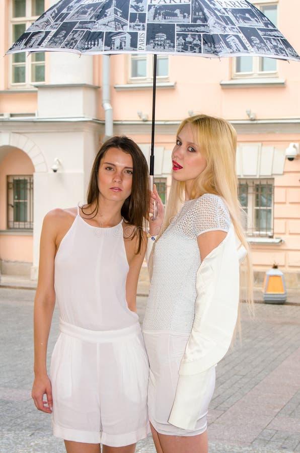 Una bionda di due amici e castana in vestiti bianchi che si nascondono dal tempo sotto un grande ombrello nei vicoli di vecchia c fotografia stock
