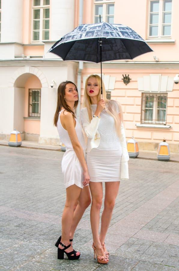 Una bionda di due amici e castana in vestiti bianchi che si nascondono dal tempo sotto un grande ombrello nei vicoli di vecchia c immagine stock
