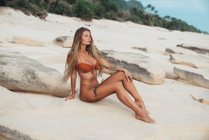 Una bionda snella con capelli spessi lunghi in un costume da bagno arancio si siede su una spiaggia bianca con gli occhi chiusi e fotografie stock