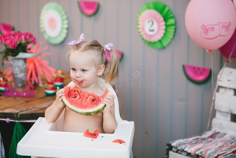 Una bionda sveglia del bambino della bambina sta mangiando un pezzo succoso di anguria che si siede in una sedia del bambino fotografia stock libera da diritti